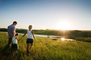 Ευχυχισμένη οικογένεια περπατά στο ηλιοβασίλεμα